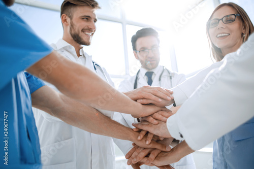 group of doctors with their hands folded together