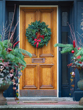 Old Wooden Front Door With Christmas Wreath Made Of Pine Branches And Red Berries