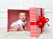 Infant Child Baby Toddler Kid Sitting In Big Red Presents Gift Box For Celebration Christmas