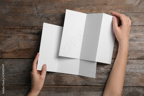 Fotografía  Woman with blank brochures on wooden background, above view