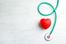 Stethoscope And Red Heart On Wooden Background, Top View With Space For Text. Cardiology Concept