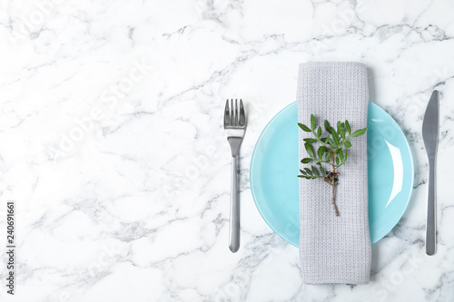 Beautiful table setting with napkin on marble background, top view. Space for text