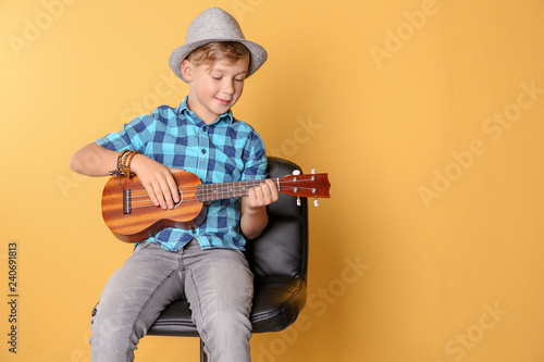 Little boy sitting on chair and playing guitar against color background. Space for text