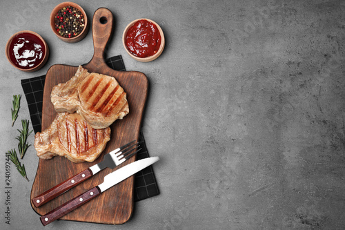 Flat lay composition with grilled meat on grey background. Space for text