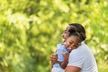 African American Father Hugging And Holding His Little Girl.