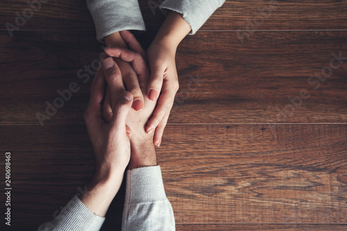Fotografering  couple hand on wooden table