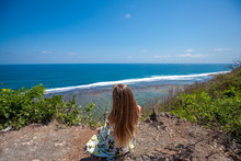 Back View Of Young Woman With Long Hair Sitting On The Edge Looking To The Horizon, Sea And Waves While Sky Is Blue On The Bali Island, Indonesia