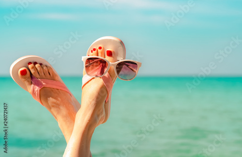 Poster de jardin Pedicure Upside woman feet and red pedicure wearing pink sandals, sunglasses at seaside. Funny and happy fashion young woman relax on vacation. Chill out girl at beach. Creative for tour agent. Weekend travel.