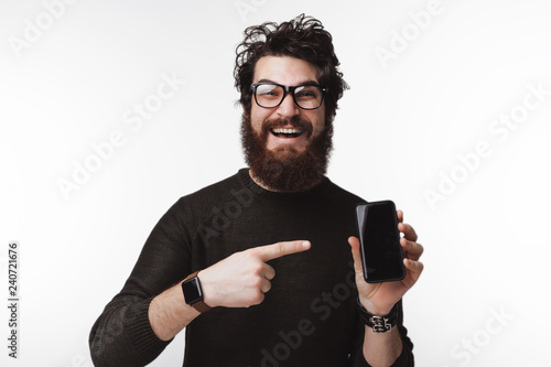 Fotografia  Photo of handsome young bearded man wearing glasses and pointing at smartphone