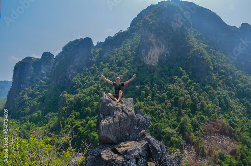 Fotografia  Achievement, man on a mountain top with rised arms!