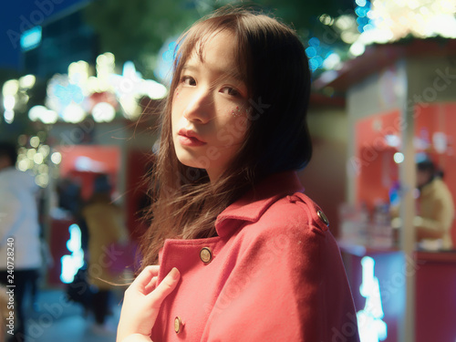 Fotografia  Night portrait of beautiful young Chinese girl in red coat looking back in Christmas market, Cool girl, beauty, emotion, expression and people lifestyle concept