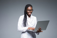 Beautiful African American Woman Doctor Or Nurse Holding A Laptop Computer Isolated On A Gray Background