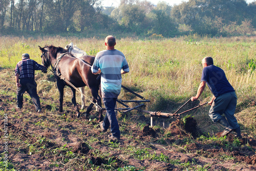 Photo Peasants plow the field with horses