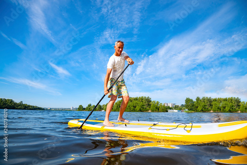 Fotografie, Obraz  Happy man is paddling on a SUP board
