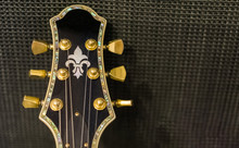 Beautiful Guitar Head With Golden Rotary Knobs And Decorative Inlay Isolated On A Music Amplifier Background