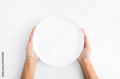 Female hands holding empty plate on white background