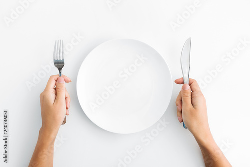 Fotografia Whte plate with silver fork and knife on white background