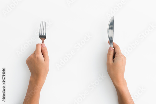 Woman hands holding fork and knife on white background