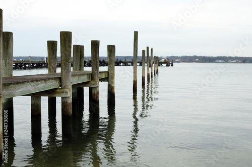 Fotobehang Crimson Coastal harbor with wooden pier dock on sandy rocky beach