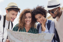 Happy Travelers Searching The Location On City Map
