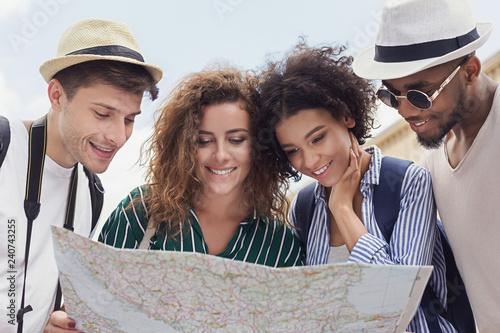 Fotografija Happy travelers searching the location on city map