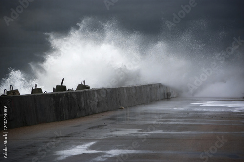 Stormy surf breaking on breakwater