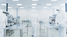 Scientist In Protective Suit Carries Case Of Finished Product Through Laboratory. Workers In The Facility With Modern Industrial Machinery. Product Manufacturing Process: Semiconductors.