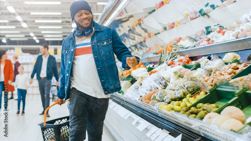 Fotografie, Obraz  At the Supermarket: Happy Stylish Guy with Shopping Basket Dances Through Fresh Produce Section of the Store