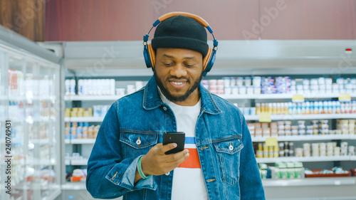 Spoed Foto op Canvas Muziekwinkel At the Supermarket: Portrait of a Stylish African American Guy with Headphones, Using Smartphone, Walks Through Frozen Goods Section of the Store.