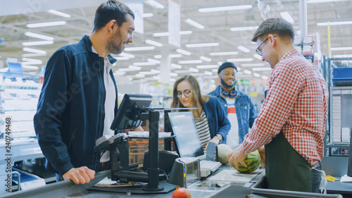 Fotografija At the Supermarket: Checkout Counter Professional Cashier Scans Groceries and Food Items