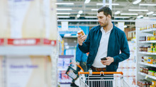 At The Supermarket: Handsome Man Uses Smartphone And Browses Through The Canned Goods Shelf. He's Standing With Shopping Cart In Canned Goods Section.