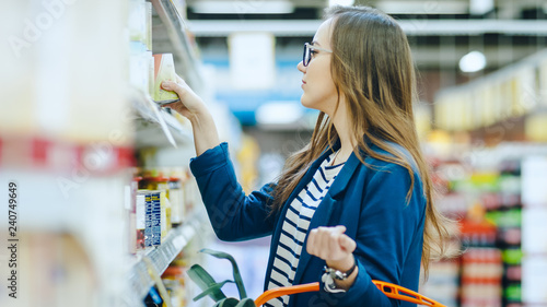 Photographie  At the Supermarket: Beautiful Young Woman Browses through the Canned Goods Section of the Store