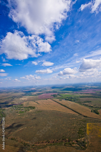 Spoed Foto op Canvas Zuid-Amerika land Flight under the clouds above the plain with rivers, fields and forests.