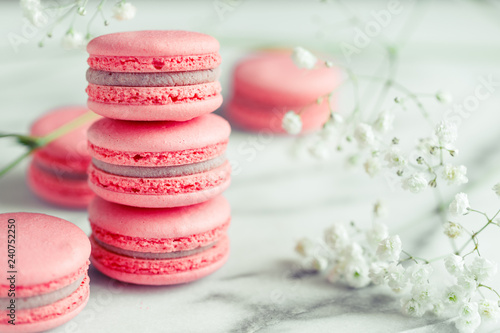 Fotobehang Macarons Stack of coral cakes macarons or macaroons on white marble with flowers besides.