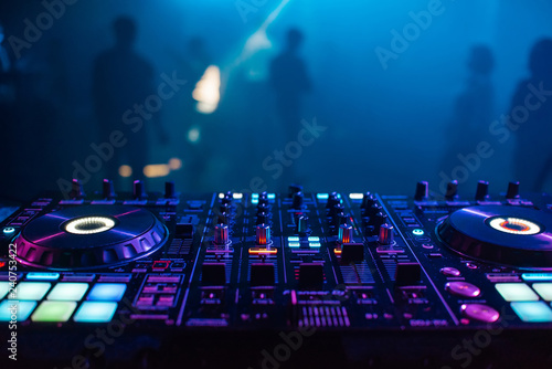 Photo  DJ mixer on the table background the night club and dancing people