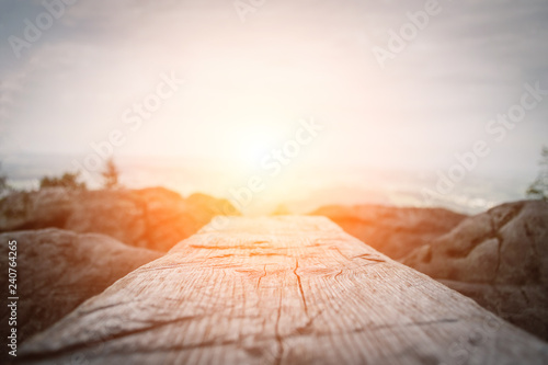 Foto  Wooden plank in front of the nature during the sunset