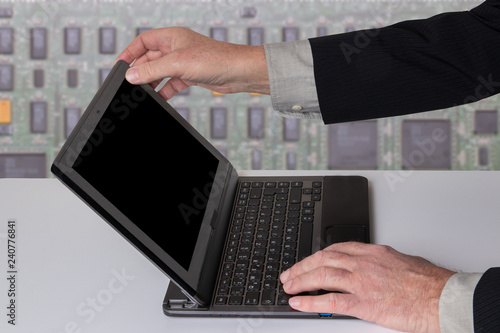 Fotografía  Hands of a unrecognizeable businessman working with a modern portable computer on a white table