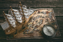 Pirate Ship, Treasure Map And A Compass On A Wooden Table Background.