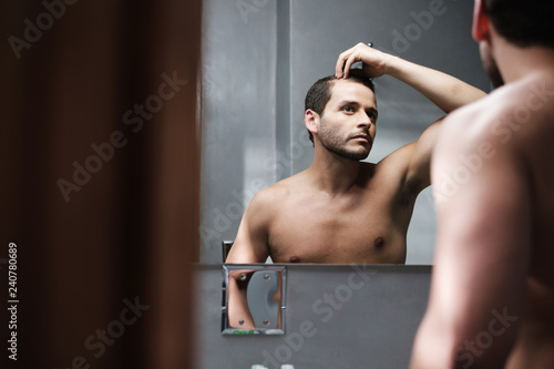 Fényképezés Young Man In Bathroom Worried About Premature Receding Hairline
