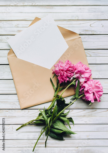 Faded purple peonies and an open kraft envelope containing a white sheet of paper. Valentine's Day concept. Copy space, top view.