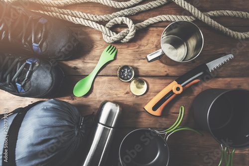 Fotografía  expedition camping equipment on wooden plank background. top view
