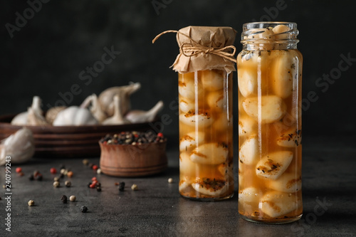 Preserved garlic in glass jars on table. Space for text