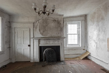 Chandelier Hanging From Ceiling In Empty Room Of Abandoned House