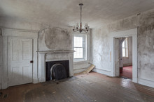 Looking Through An Empty Room Of An Abandoned House With Vintage Fireplace