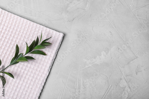 Fabric napkin and twig with green leaves on gray background, top view. Space for text