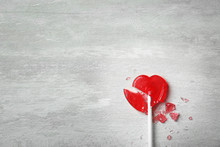 Broken Heart Shaped Lollipop On Gray Background, Top View With Space For Text. Relationship Problems