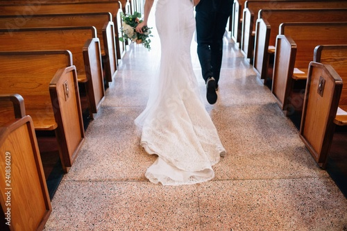Fotomural  bride and groom walking down church aisle after ceremony