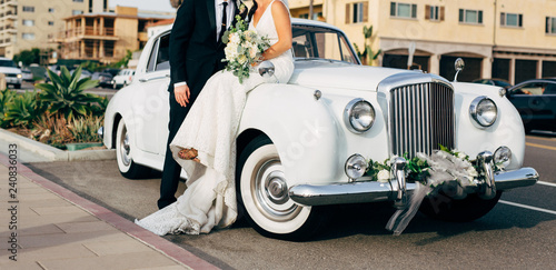 Fotografia  bride and groom next to classic car on street kissing