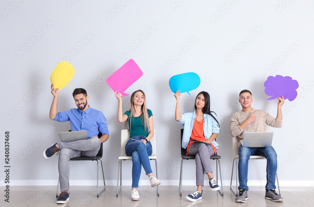 Fototapeta Young people with blank speech bubbles sitting near white wall