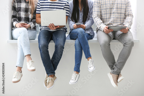 Fotografía  Young people with modern devices sitting on windowsill indoors